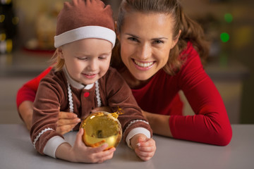 Portrait of smiling mother and baby holding christmas ball