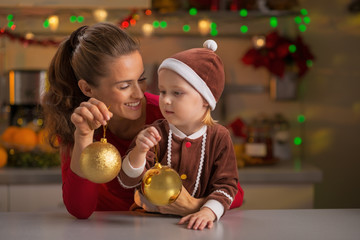 Portrait of mother and baby holding christmas balls