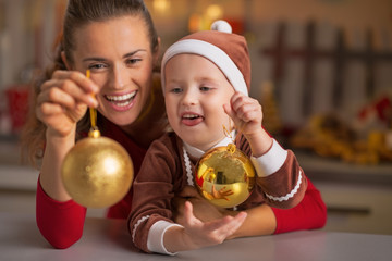 Portrait of smiling mother and baby holding christmas balls