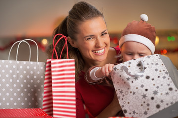 Mother and baby looking in christmas shopping bags