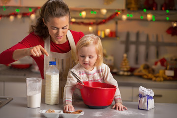 Happy mother and baby making christmas cookies in kitchen