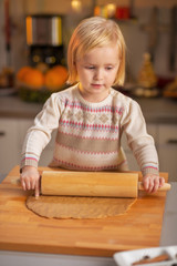 Portrait of baby rolling dough in christmas decorated kitchen