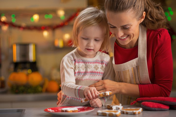 Portrait of smiling mother and baby making christmas cookies