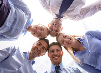 smiling group of businesspeople standing in circle