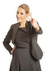 Happy businesswoman showing victory sign