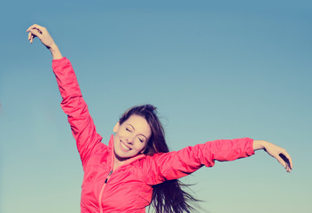 Woman smiling arms raised up to blue sky, celebrating freedom