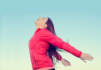 Woman smiling arms raised looking at blue sky taking deep breath