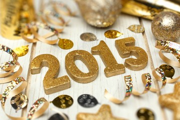 2015 New Years Eve golden numbers with decorations on white wood