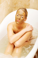 Woman sitting in a bath with face mask