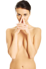 Front view of serious nude woman holding nose