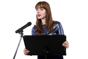 girl in shiny dress speaking on a microphone in a podium