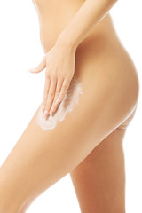 Close up woman applying a cream on leg