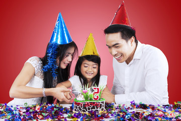 Attractive family cutting a birthday cake
