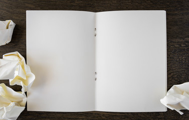 Note book with  crumpled paper on a wooden desk