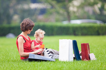 Mother and daughter resting on the lawn after shopping