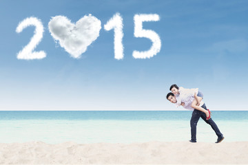 Cheerful couple piggyback on beach