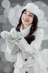 Cheerful woman playing snowfall