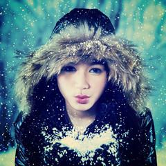Excited teenage girl blowing snow