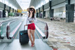Female tourist on escalator at airport 1