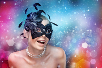 Young woman with black masquerade mask with feathers