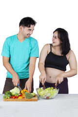 Man and pregnant woman preparing salad