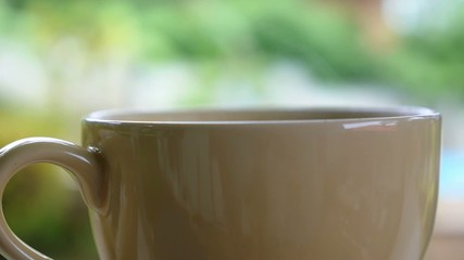Close up of Steaming Tea Cup on the Blurred Green.