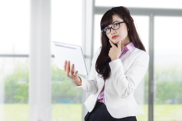 Thoughtful businesswoman holding digital tablet 1