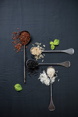 Vintage spoons with red, brown, white and black rice, above view