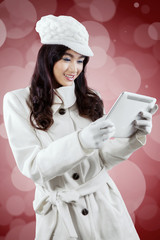 Young woman in winter jacket with tablet