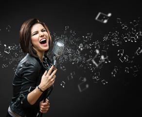 Portrait of female singing rock musician on grey background