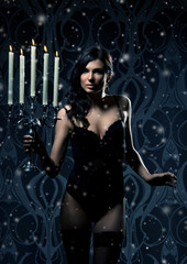 Fashion shoot of a young sexy woman in lingerie holding candles