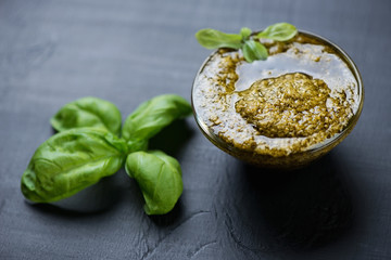 Basil pesto on a black rustic wooden surface, studio shot
