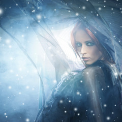 Young woman in blowing silk on a snowy background