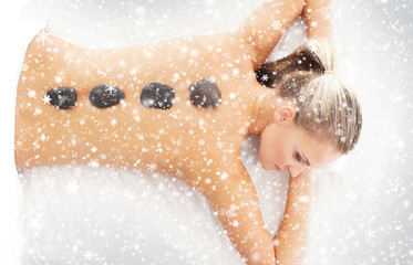 Woman getting hot stone treatment on the snow