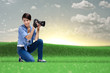 Creative girl-photographer takes snapshots on the meadow