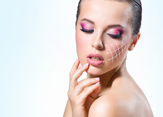 Massage lines on the girl face, on blue background