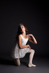 Image of smiling young ballerina posing in studio