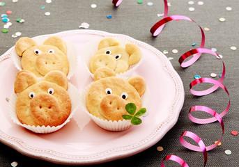 Tasty cute pig cookies with leaves on pink plate