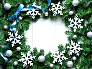 Snow flakes with ribbon on fir leaves.frame