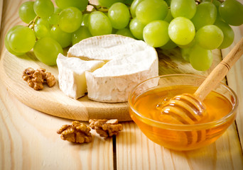 Still life of cheese, honey, walnuts and grapes