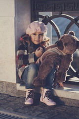 Little girl in a pink beret holds a toy bear, toning