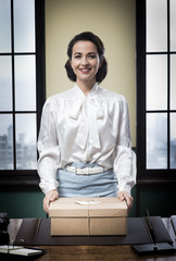 Cheerful secretary holding a mail package