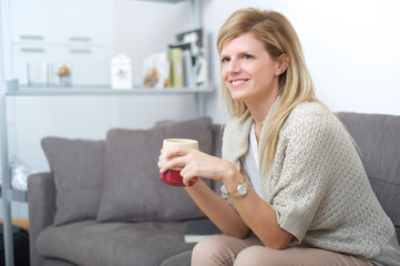 woman drinking a cup of the on sofa