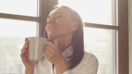 Young smiling woman having a cup of tea, coffee