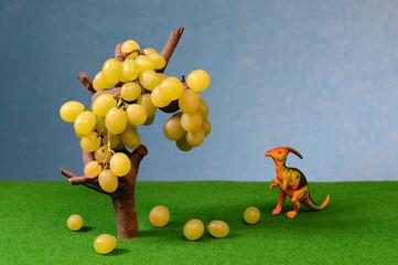 White fresh grapes and dinosaur figure