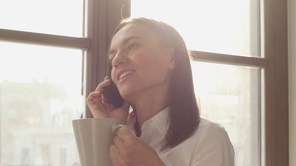 Attractive woman drinking coffee and talking on cellphone