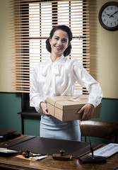 Smiling young secretary holding a mail package