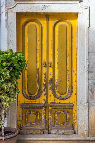 Typical yellow doorway in the old town of Olhao - 73560872