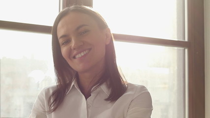 Portrait of a beautiful smiling brunette at the window