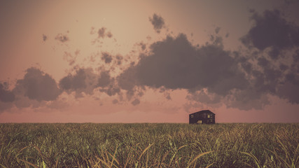 Old abandoned wooden barn on prairie at sunset with cloudy sky.